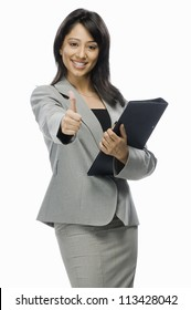 Portrait of a businesswoman holding a file and showing thumbs up