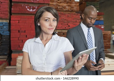 Portrait of businesswoman holding tablet PC while colleague using cell phone