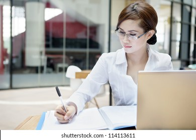 Portrait of businesswoman with laptop writes on a document at her office