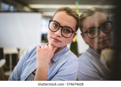Portrait of businesswoman leaning on glass in creative office