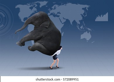 Portrait of businesswoman lifting heavy elephant over world map