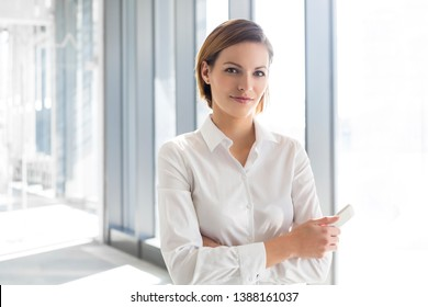 Portrait of businesswoman with mobile phone standing at office