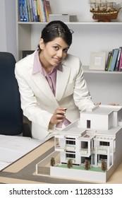 Portrait of a businesswoman near a model home in an office