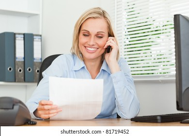 Portrait of a businesswoman reading a letter while phoning