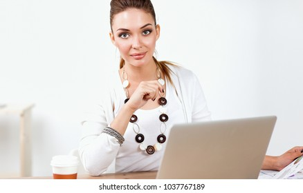 Portrait of a businesswoman sitting at  desk with  laptop