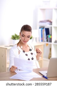 Portrait of a businesswoman sitting at a desk with a laptop, isolated