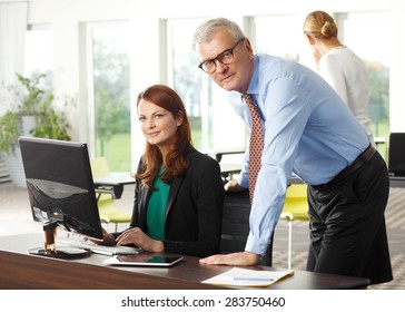 Portrait of businesswoman sitting at office in front of laptop while sales woman and senior businessman consulting. Teamwork at office.