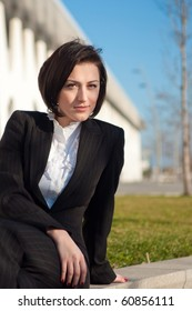 Portrait of a businesswoman sitting and posing outdoors