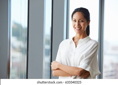 Portrait Of Businesswoman Standing By Window In Office
