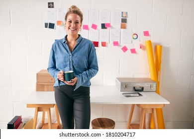 Portrait Of Businesswoman Standing In Front Of Designs And Desk In Start Up Fashion Business