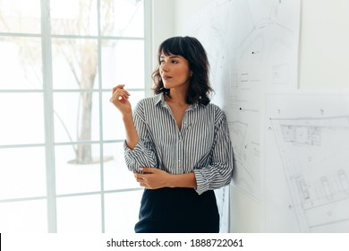 Portrait of businesswoman standing in office. Female manager standing beside architecture drawings on wall chart in office.
