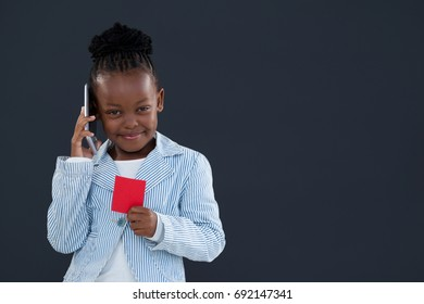 Portrait of businesswoman talking on phone while holding red card against gray wall in office