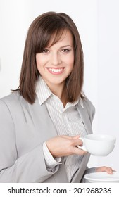 Portrait of businesswoman with white cup and saucer, isolated on white
