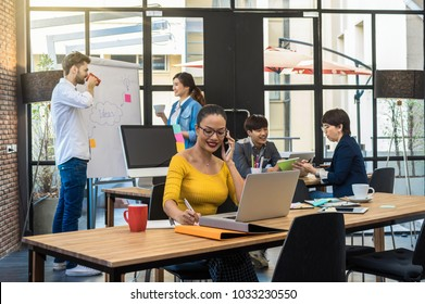 Portrait of Businesswoman working with computer over the photo blurred of Group Of Asian and Multiethnic Business people with casual suit in the modern Office, people business group concept