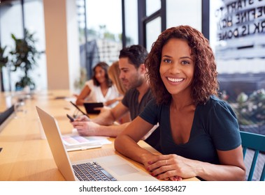 Portrait Of Businesswoman Working At Desk In Shared Open Plan Office Workspace