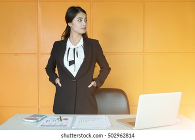 Portrait of a businesswoman working at office with laptop and document on table.