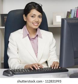 Portrait of a businesswoman working on a desktop PC in an office