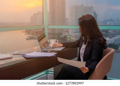 Portrait of businesswoman working on laptop writes on a document, taking notes at modern office.