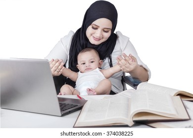 Portrait of businesswoman working and playing with her baby boy at home