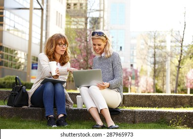 Portrait of businesswomen sitting at office park while using digital tablet and laptop. Business team working online togetherness while consulting.