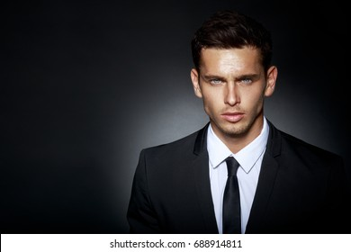 Portrait of a bussines man, wearing in black elegant suit looking at camera, isolated on black background. Horizontal view.