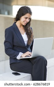 Portrait of a bussines woman working with laptop. She is wearing a black suit.