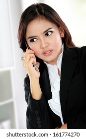 Portrait of busy business woman using a mobile phone at her office