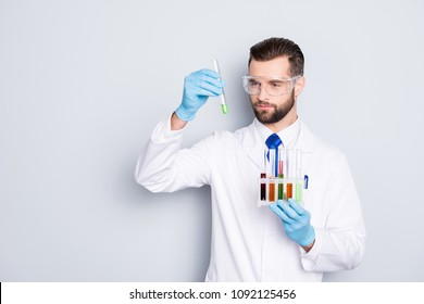 Portrait of busy concentrated scientist with stubble in white lab coat, gloves analysing, looking at  test tubes with multi-colored liquid in his arm, isolated on grey background