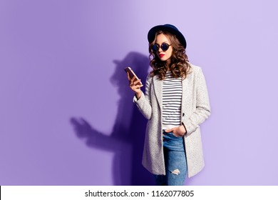 Portrait of busy cool business woman in jeans overcoat striped outfit having smart cell phone in hand using wi-fi 3G internet checking email searching contact isolated on violet background
