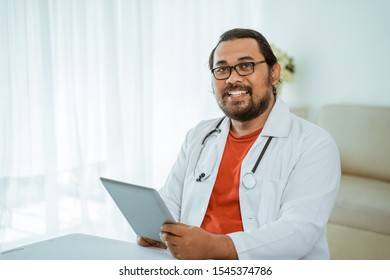 portrait of busy doctor using tablet pc in his office and smiling to camera