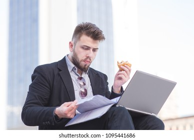 Portrait of busy man with laptop, business papers and snack in hand in the open air. A busy businessman works on the street.