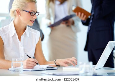 Portrait of busy secretary looking at laptop while networking