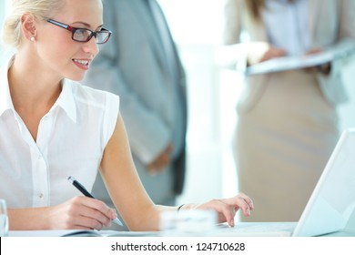 Portrait of busy secretary typing in working environment
