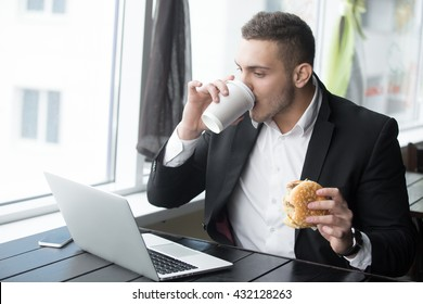 Portrait of busy young business man sitting with glass of drink and hamburger in fast food restaurant interior. Attractive caucasian man eating and using notebook computer in cafe. Indoors