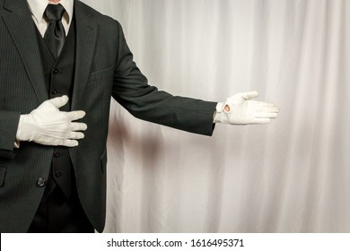 Portrait of Butler in Dark Suit and White Gloves in a Welcoming Gesture. Service Industry. Professional Hotel Hospitality and Courtesy. Copy Space for Service.