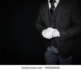 Portrait of Butler or Servant in Dark Suit and White Gloves Ready to Help on Black Background. Service Industry. Professional Hospitality and Courtesy. Formal White Glove Service.