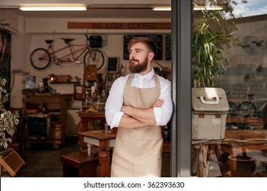 Portrait of a cafe owner standing in the doorway of his coffee shop. Young waiter standing with his arms crossed at the door of a restaurant and looking away.