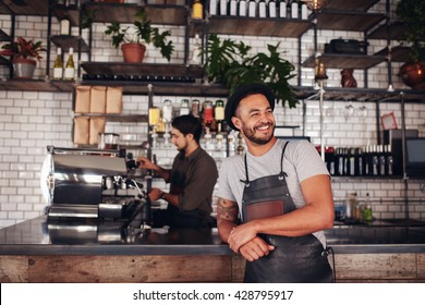Portrait of cafe owner wearing a hat and apron standing at the counter and looking away. Barista working in background behind the counter making drinks.