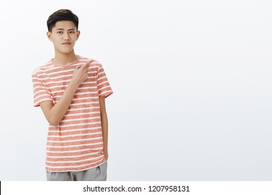 Portrait of calm attractive young teenage asian guy with dark short hairstyle in striped t-shirt holding hand in pocket pointing at upper right corner while standing relaxed and chill over grey wall