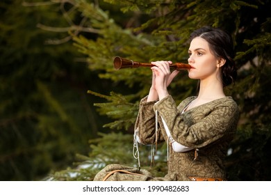 Portrait of Calm Caucasian Female in Old Medieval Green Dress Playing The Flute Against Firtrees Outdoors. Horizontal Image Composition