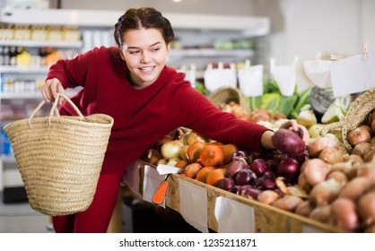 Portrait of calm female customer selecting onions in grocery shop