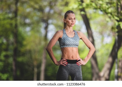 Portrait of calm lady is standing among marvelous green landscape. She is wearing sports clothes and looking ahead. Solitude in nature concept
