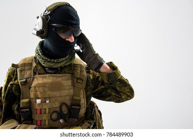 Portrait of calm peacemaker in military uniform telling by headphone. Army and communication concept. Isolated and copy space
