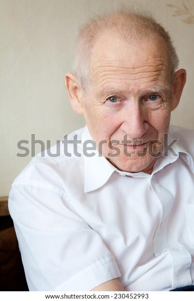 portrait of a calm senior man in white shirt