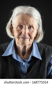 Portrait of a calm senior woman looking at the camera. Over black background.