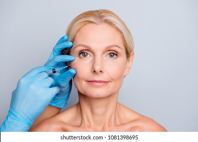 Portrait of calm serious charming aged woman with wrinkle getting injection in cheek in professional clinic hands in gloves making face contouring isolated on grey background