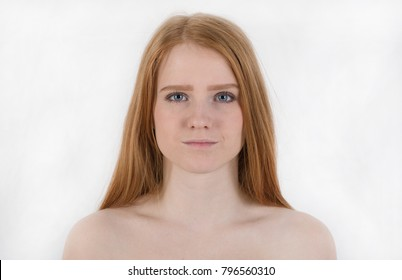 Portrait of a calm and sexy young woman with flowing red hair and bare shoulders, looking forward with blue eyes isolated on the white background.Positive human emotions and feelings. European woman