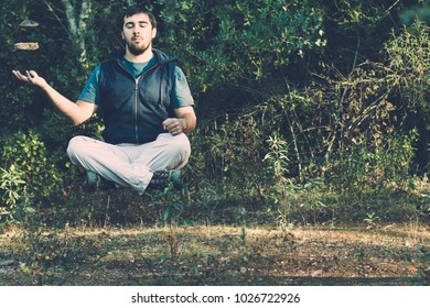 Portrait of a calm Young boy man levitating outdoors in the forest but also levitating some rocks with mind tricks. Concept