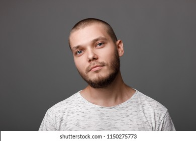 portrait of calm young man on gray background