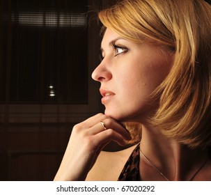 Portrait of a calm young woman sitting inside dark room with romantic light